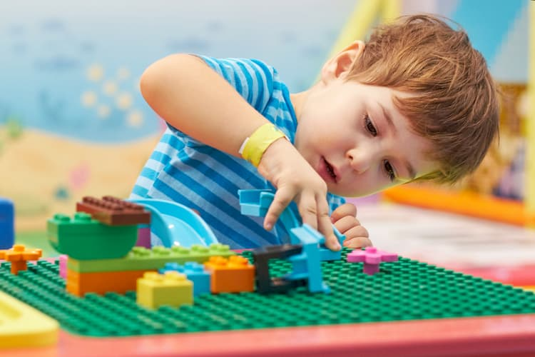 child playing and building with colorful plastic bricks table