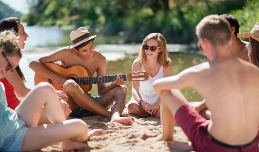 a group of young people playing music on the beach