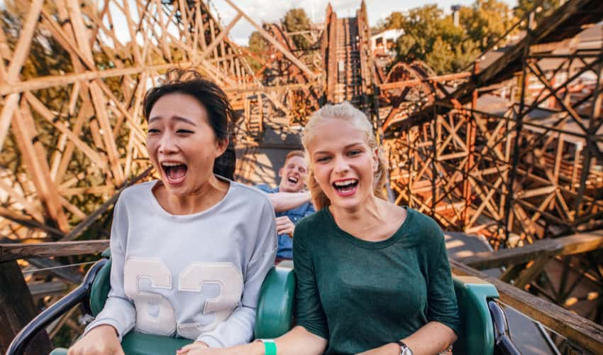 Two women laughing and riding a wooden rollercoaster