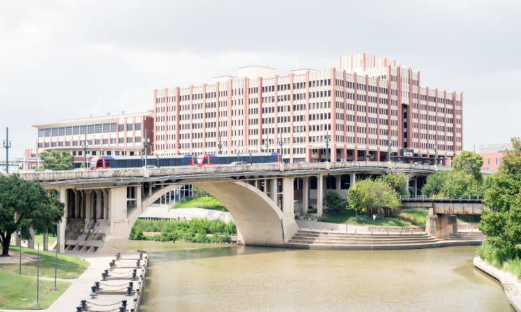 view across the river of a train passing in front of a University of Houston building