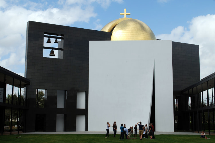 A campus tour group admires the Chapel of St. Basil at University of St. Thomas