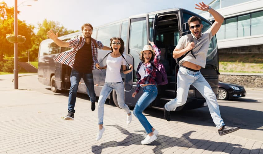 four charter bus passengers jump in the air and cheer before a road trip