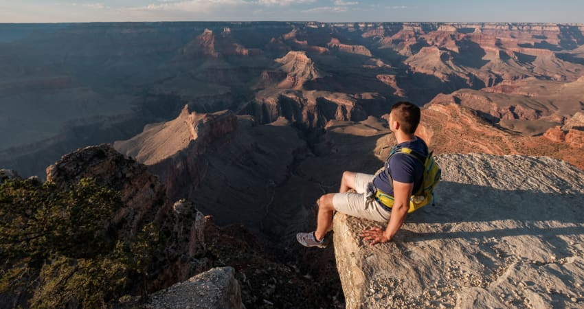 a tourist sits on the rim of the Gran Canyon and watches the sun set