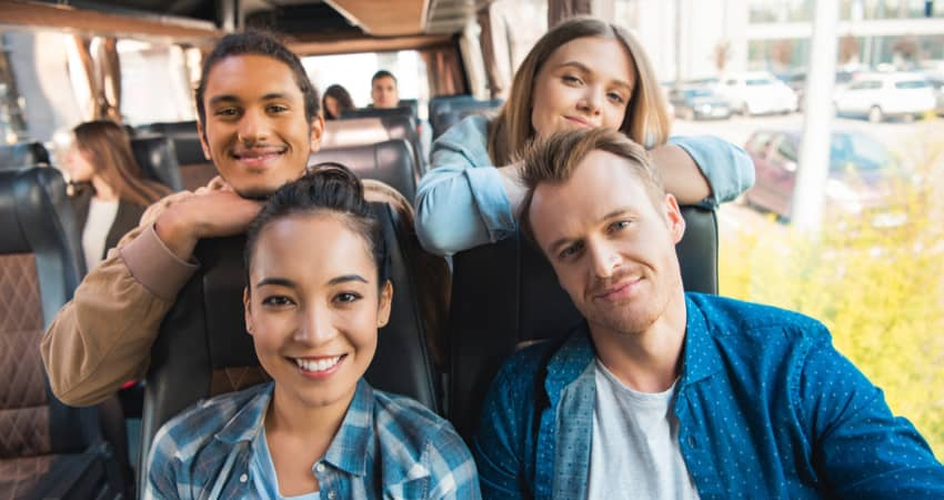 A group of young tourists smiling on a charter bus