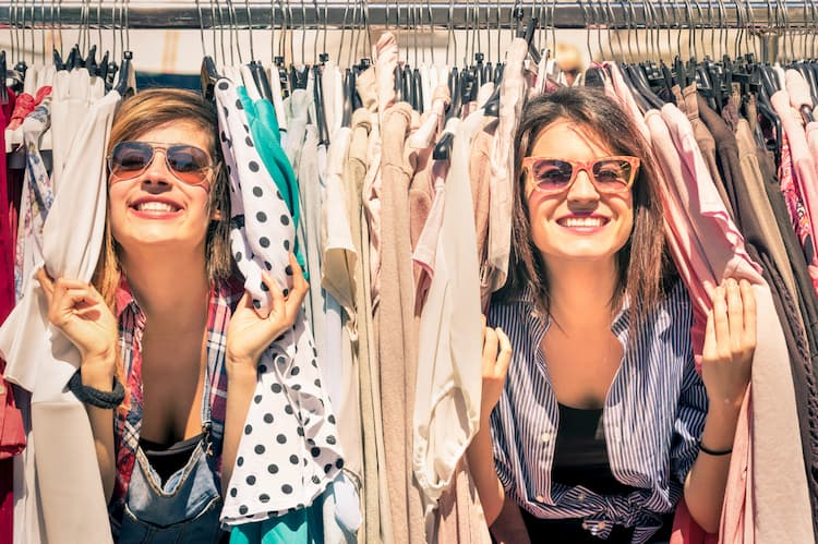 Best friends shopping in clothing rack on sunny day.