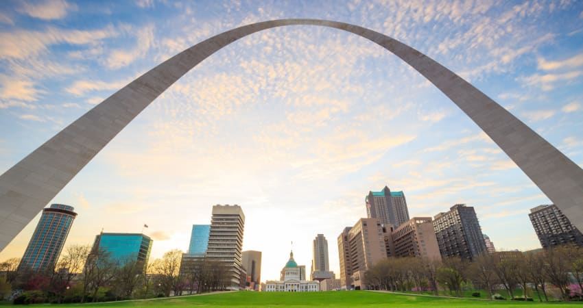 the Gateway Arch towers over the skyline and sunset in St Louis