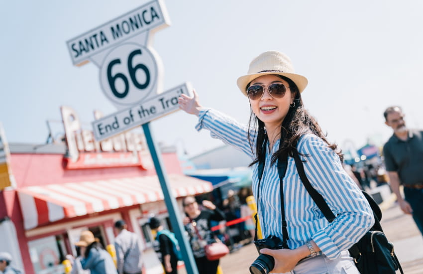 a woman with a camera poses for a photo by the Route 66 sign in Santa Monica