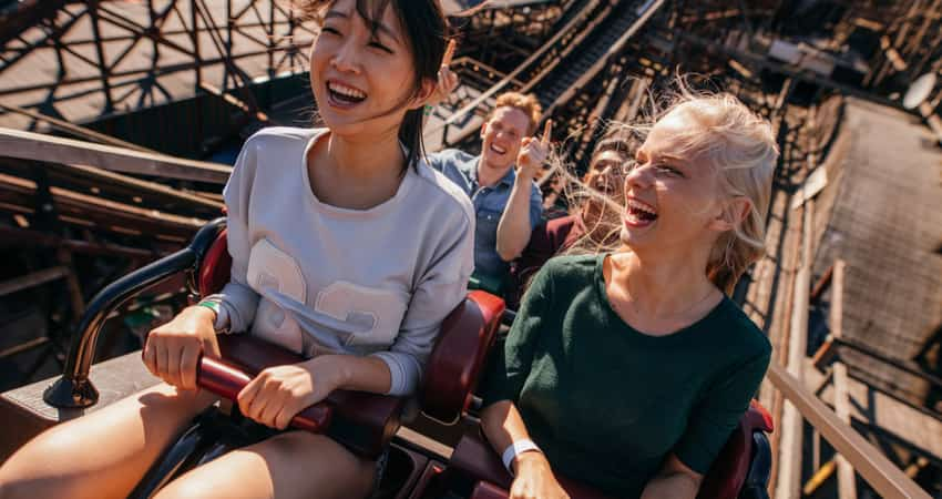 Friends smiling on a wooden roller coaster