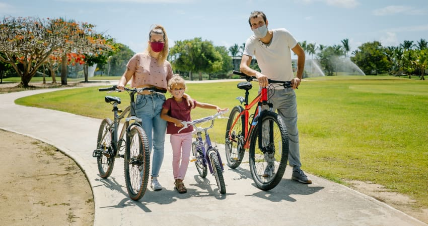 a family of three ride bikes on. paved trail while wearing masks