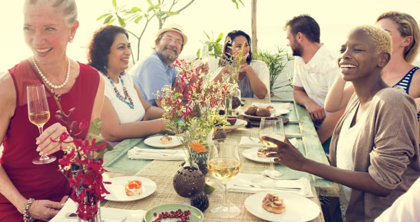 A group of friends gather around the table, talk, and drink white wine