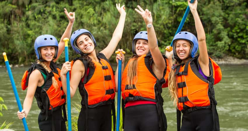 A group of young women smiling in rafting gear with paddles