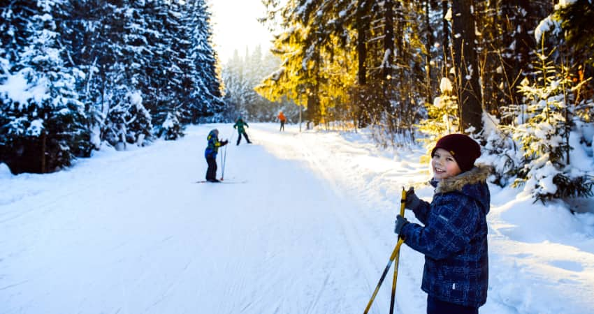 A child and his friends ski along a tree-lined trail