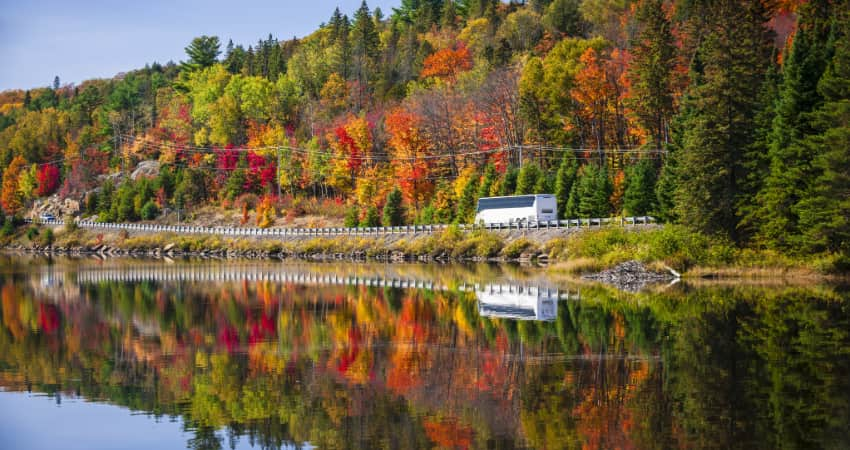 a bus drives past beautiful fall scenery on a byway