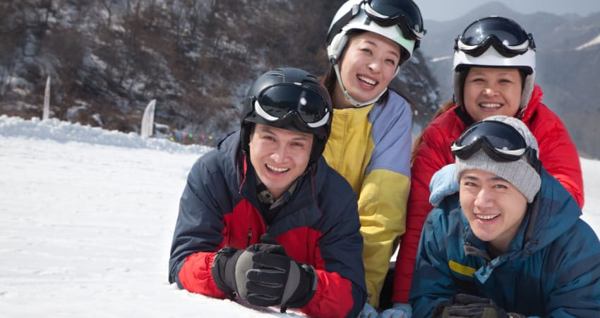 two couples pose for a picture in the snow on a ski slope