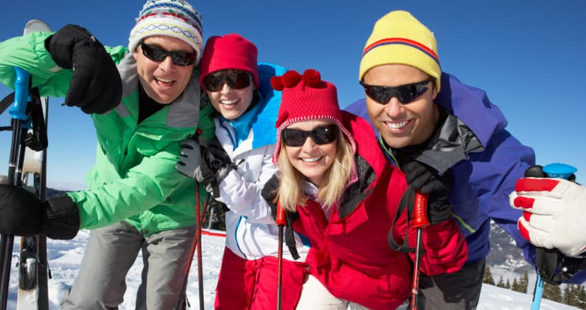 two couples stand and pose for a photo on a snowy peak with skis ready