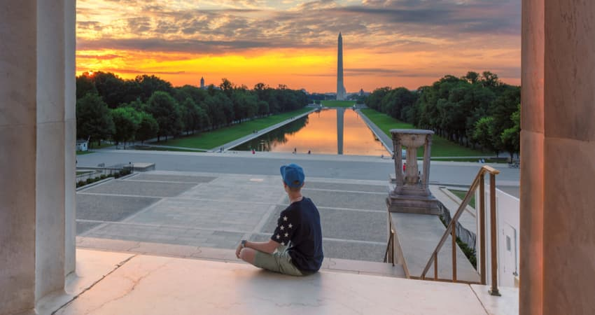 A person sitting at the Lincoln Memorial at sunset