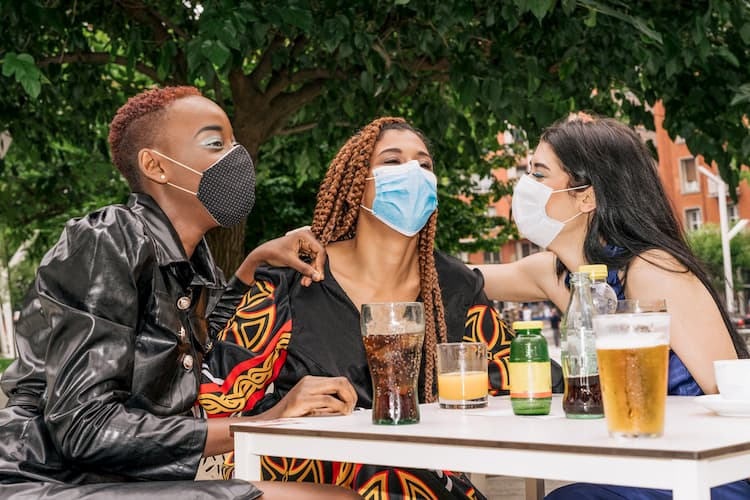 People with drinks in masks