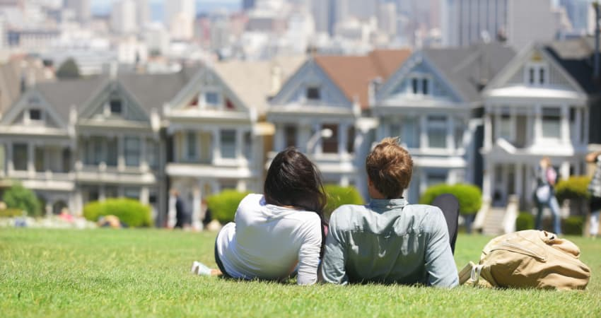 A couple lay on the grass in Alamo Square park, near the Painted Ladies