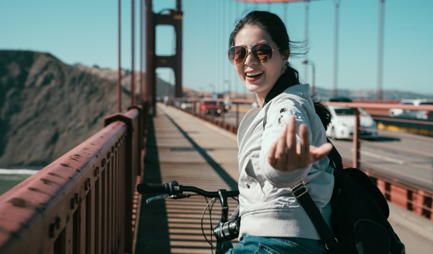 A woman on a bike crosses the Golden Gate Bridge