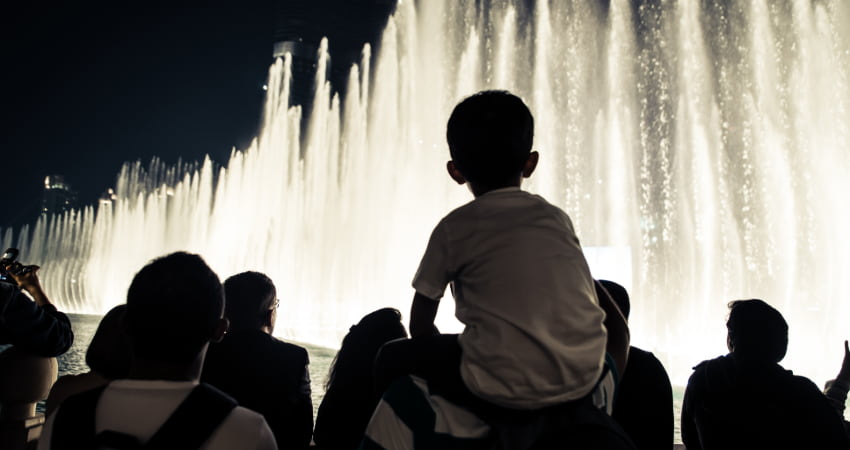 A child sits on their parent's shoulders as they watch the Bellagio Fountain show at night