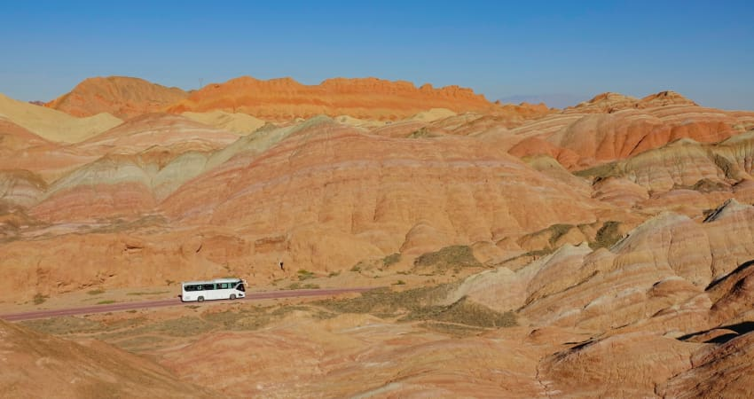 A lone charter bus drives through the desert, rock formations in the distance