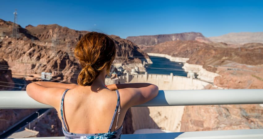 A lone woman stands at an overlook railing, looking down on the Hoover Dam and Lake Mead