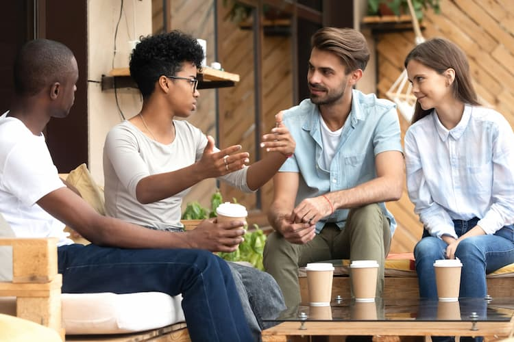 Friends talking over coffee on outdoor patio