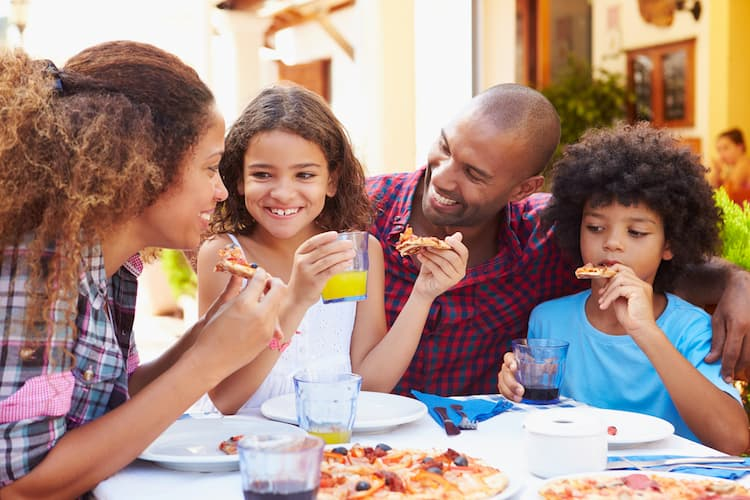 Family eating pizza on outdoor patio