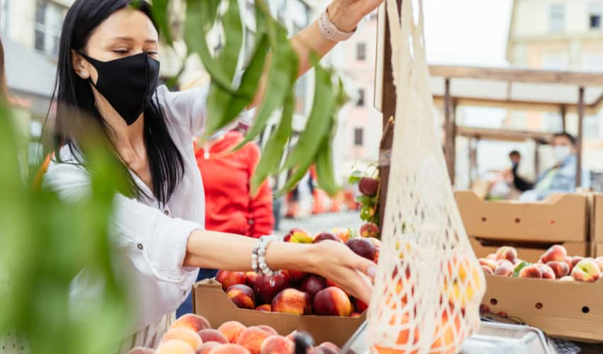A woman wearing a mask and shopping for fruit at a farmers market