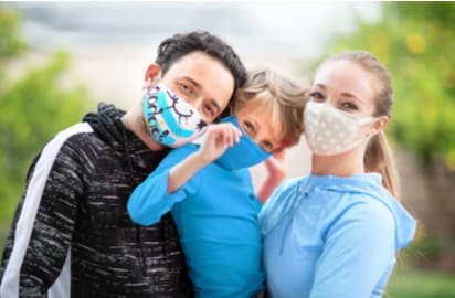 A family taking a photo with masks on