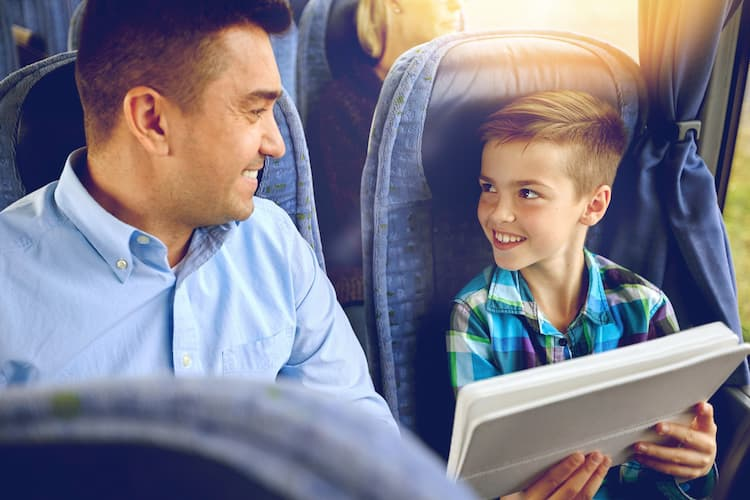 Son showing dad picture on a charter bus
