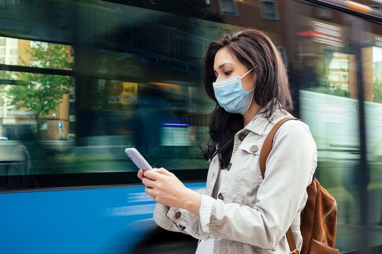 Woman waiting on bus with phone and mask