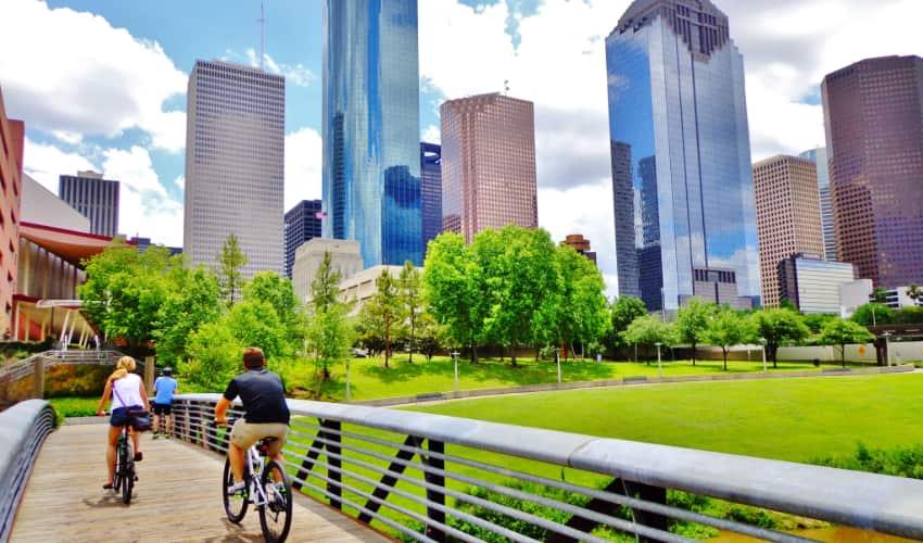 Two people ride bikes on the Buffalo Bayou Hike and Bike Trail in Houston