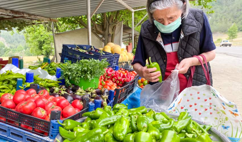 A woman wearing a mask weighs peppers on a scale in a farmers market