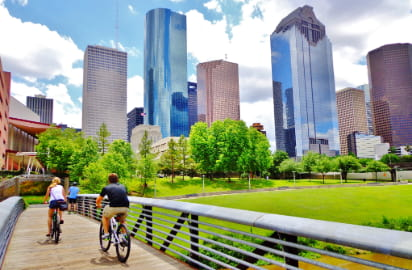 Two people ride bikes on the Buffalo Bayou Hike and Bike Trail in Houston