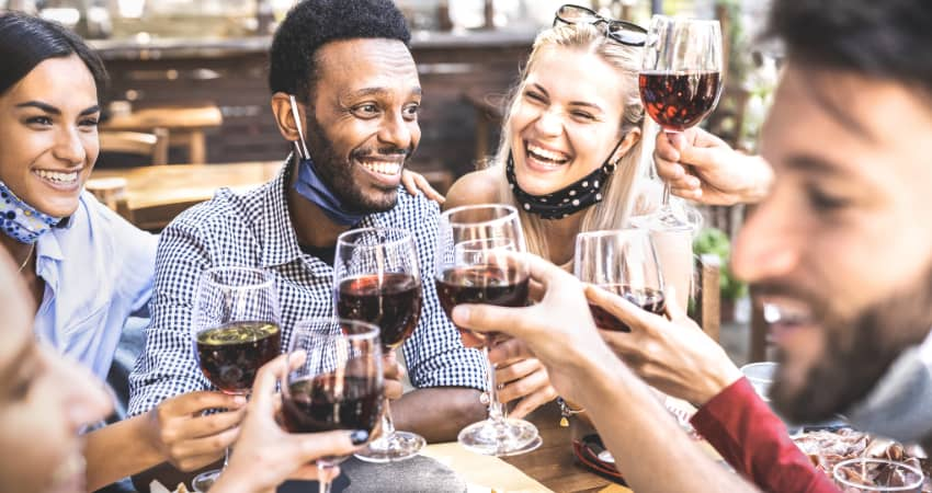 A group of friends toasting glasses of red wine