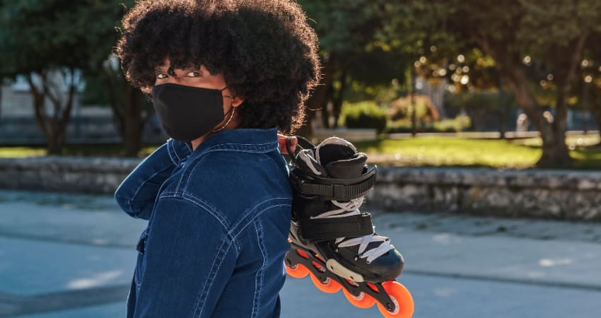 A woman wearing a mask carries a pair of rollerblades in a green public park