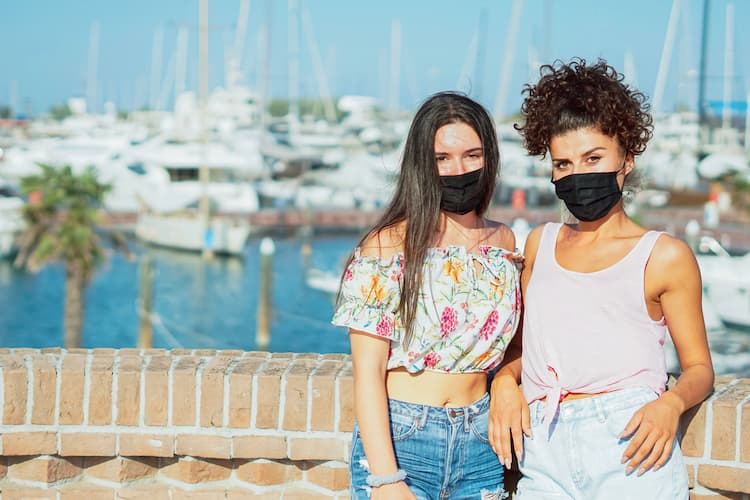 Two women wearing masks in front of ocean