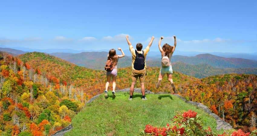 People jumping in the air at the top of a mountain along the Blue Ridge Parkway in Asheville