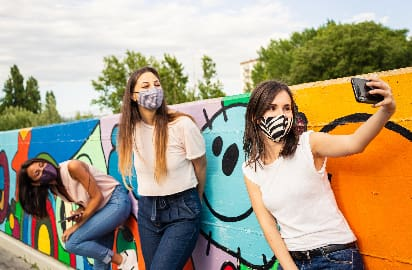 Three friends wearing face coverings pose for a selfie in front of a bright outdoor mural