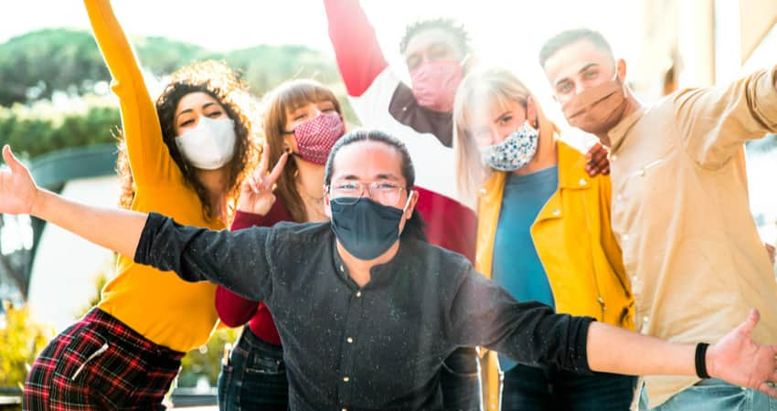 A group of friends outside wearing masks