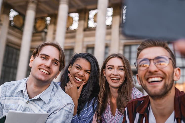 four friends smile for the camera in front of a historic building