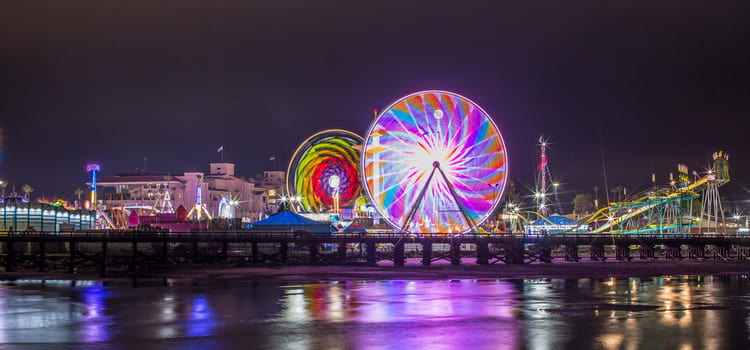 two ferris wheels in a long-exposure photograph of a pier in del mar