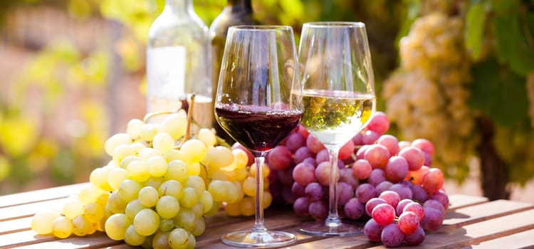 two wine glasses, one with red and one with white wine, arranged in front of a bunch of grapes on an outdoor table