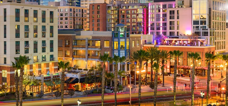 a view of a shopping and apartment complex in san diego, lit up at dusk