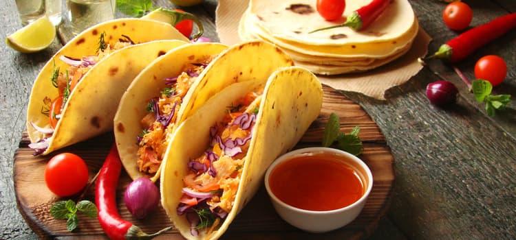 3 tacos arranged on a wooden platter at a restaurant