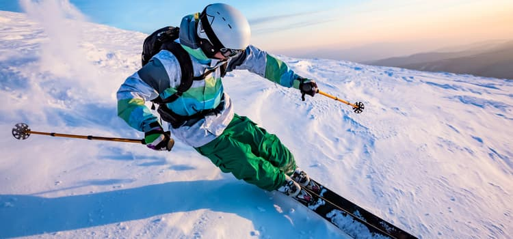 a skiier leans into a turn while traveling down a snowy hillside
