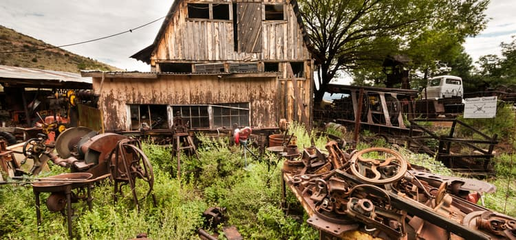 a wooden house with old metalworking project sitting in the front among the tall grass