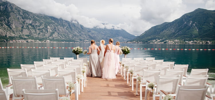 Bride and bridesmaids in front of lake and mountains with wedding chairs framing image