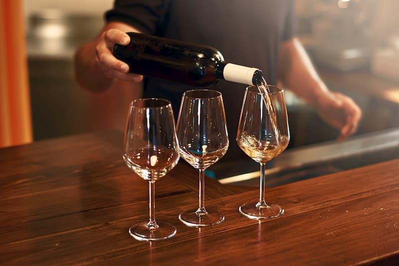 Person pouring wine into glasses